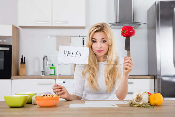 Frustrated Woman Holding Help Flag In Kitchen Stock photo © AndreyPopov