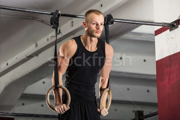 Fitness Man Training Arms With Gymnastics Rings Stock photo © AndreyPopov