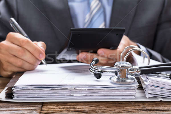 Businessman Calculating Invoice With Stethoscope On Documents Stock photo © AndreyPopov