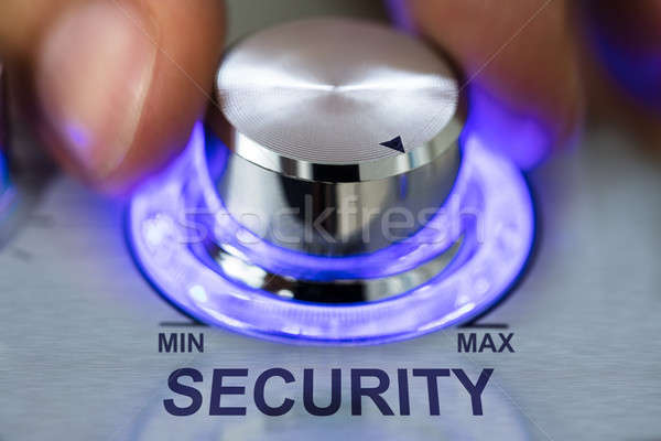 Hand Turning Metallic Illuminated Knob By Security Text Stock photo © AndreyPopov