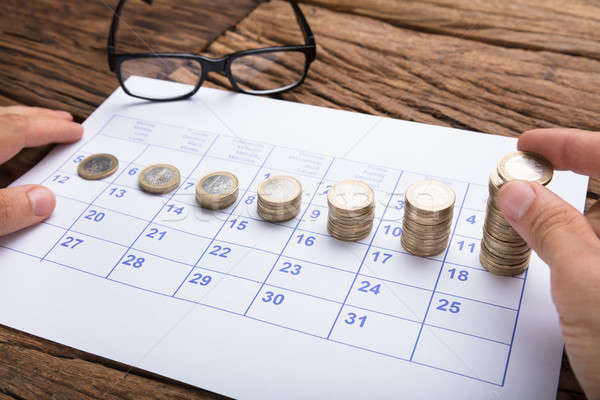 Businessman Stacking Coins In Increasing Order On Calendar Stock photo © AndreyPopov