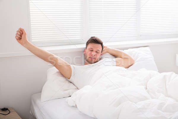 Man Stretch His Hand After Wake Up Stock photo © AndreyPopov