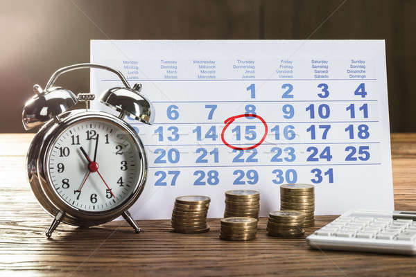 Circle Marked On Calendar With Clock And Coins On Desk Stock photo © AndreyPopov