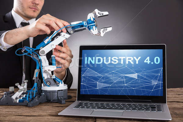 Businessman Building Robot With Laptop Showing Industry 4.0 Stock photo © AndreyPopov
