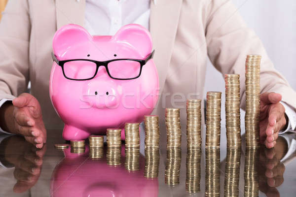 Businesswoman Protecting Stacked Coins And Piggy Bank Stock photo © AndreyPopov