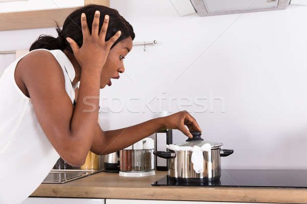 Stock photo: Woman Looking At Spilling Out Boiled Milk From Utensil