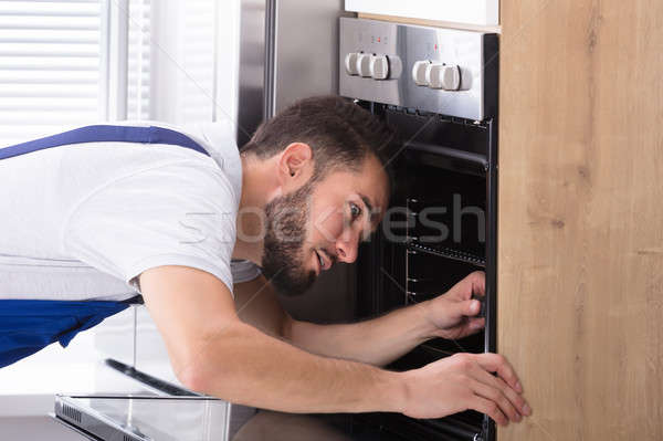Electrician Repairing Oven With Screwdriver Stock photo © AndreyPopov