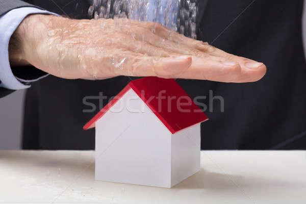 Kéz ház modell zuhan víz közelkép Stock fotó © AndreyPopov