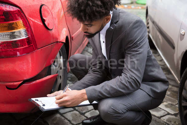 Insurance Agent Writing On Clipboard After Car Accident Stock photo © AndreyPopov