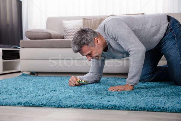 Stock fotó: Férfi · néz · szőnyeg · nagyító · oldalnézet · érett · férfi