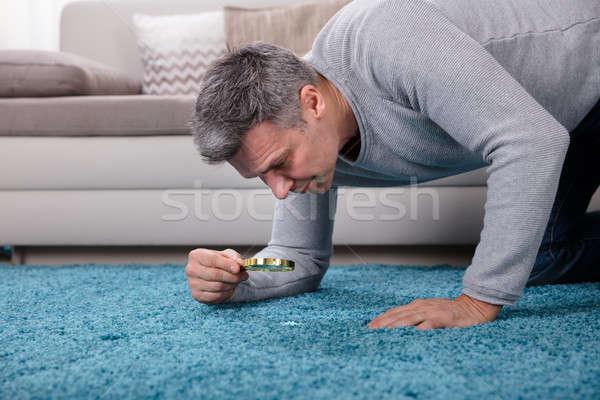 Férfi néz szőnyeg nagyító oldalnézet érett férfi Stock fotó © AndreyPopov