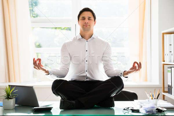 Businessman meditating in lotus position Stock photo © AndreyPopov