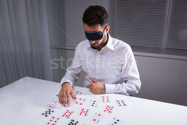 Blindfolded Businessman Reading Cards In Office Stock photo © AndreyPopov