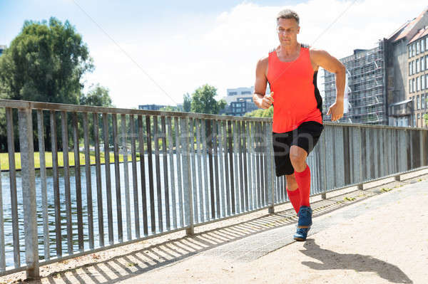 Mature Athletic Man Running On Sidewalk Stock photo © AndreyPopov