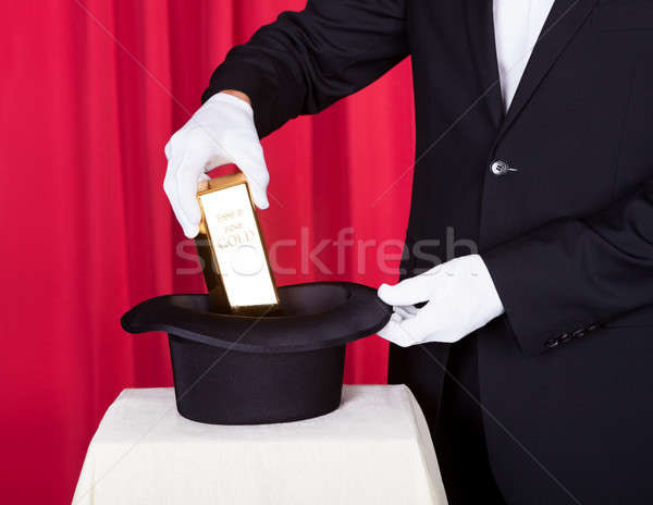 Magician Removing Bullion From Hat Stock photo © AndreyPopov