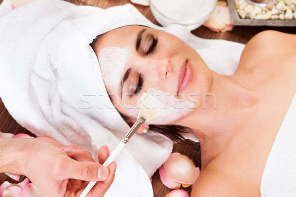 Beautiful young woman getting facial mask Stock photo © AndreyPopov