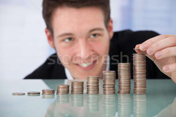 Happy Businessman Stacking Coins In Increasing Order Stock photo © AndreyPopov