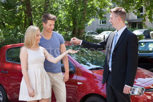Salesman Giving Key To Couple By Car Stock photo © AndreyPopov