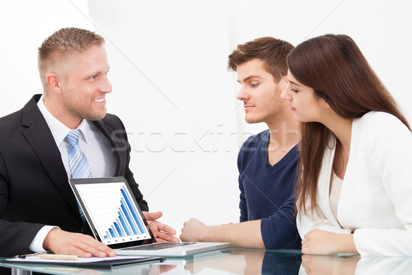 Advisor Showing Investment Plans To Couple On Laptop Stock photo © AndreyPopov