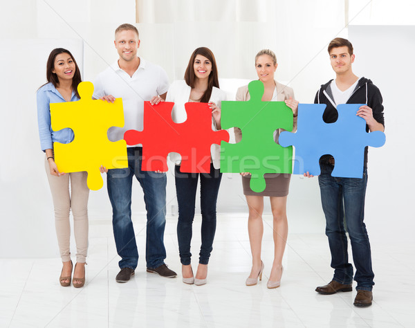 Stock photo: Confident Businesspeople Joining Puzzle Pieces