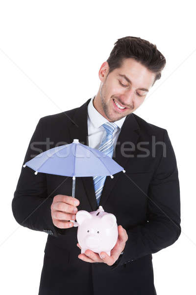 Businessman Sheltering Piggybank With Umbrella Stock photo © AndreyPopov