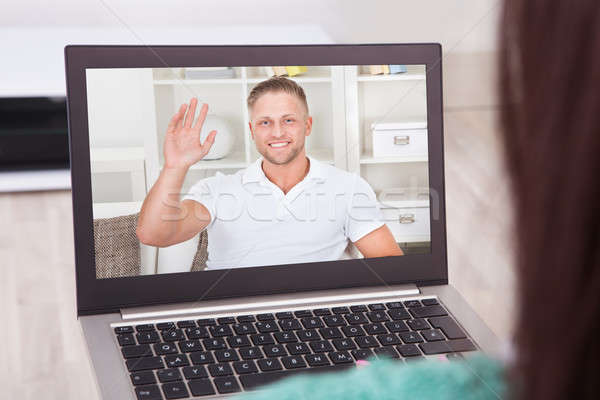Video conferencing with friend on laptop from home Stock photo © AndreyPopov