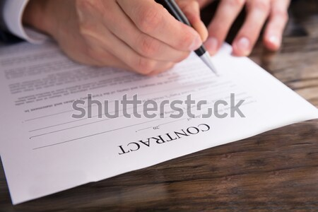 Businessman Signing Contract Paper At Desk Stock photo © AndreyPopov
