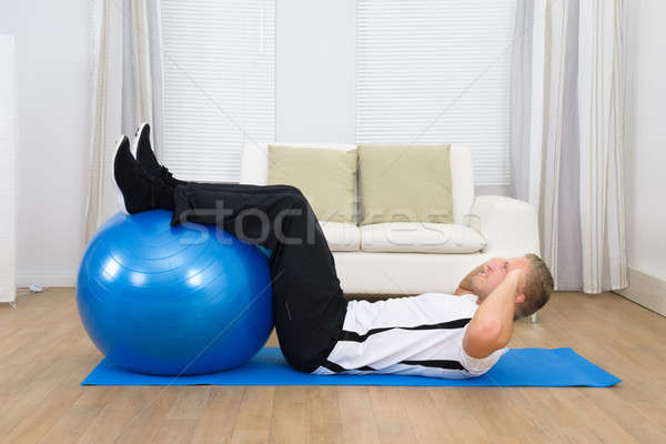 Man Doing Exercise With A Pilates Ball Stock photo © AndreyPopov