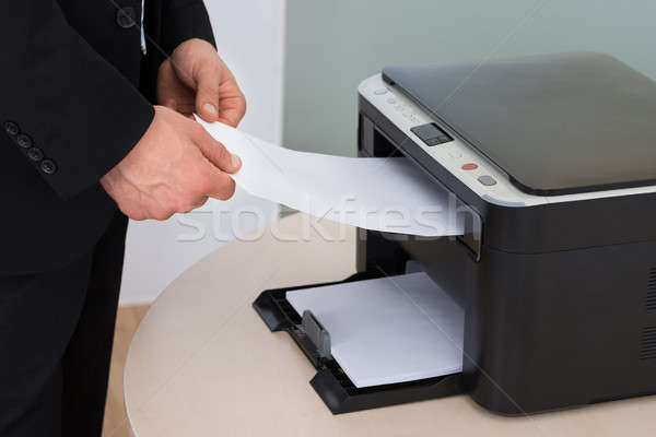 Businessman Holding Paper While Using Photocopy Machine Stock photo © AndreyPopov