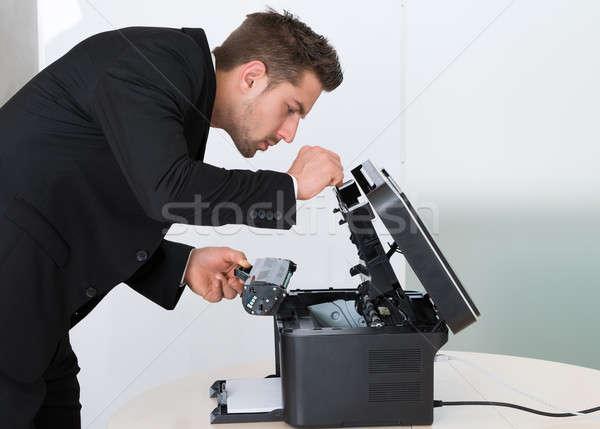 Fiatal üzletember megjavít patron gép oldalnézet Stock fotó © AndreyPopov