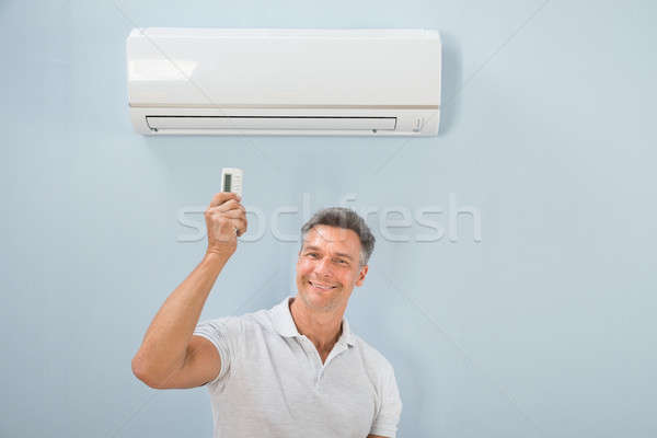 Man Operating Air Conditioner Stock photo © AndreyPopov