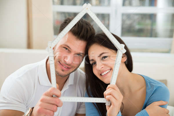 Young Couple With Model House Made Up Of Measurement Tape Stock photo © AndreyPopov
