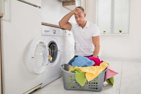 Tired Man Loading Clothes Into The Washing Machine Stock photo © AndreyPopov