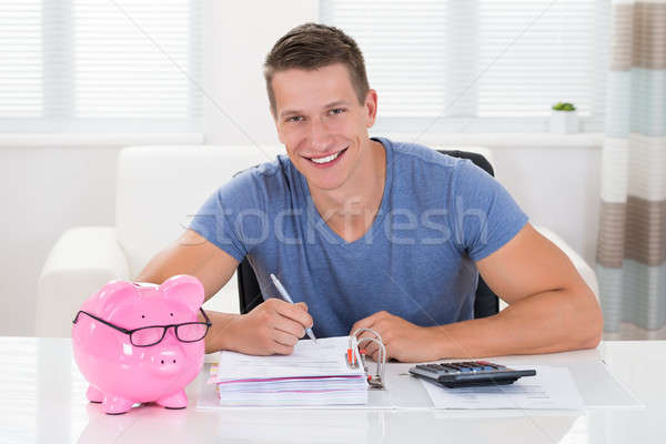 Man With Piggybank Calculating Receipt Stock photo © AndreyPopov