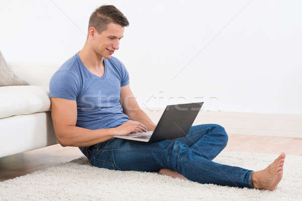 Man With Laptop Sitting On Carpet Stock photo © AndreyPopov