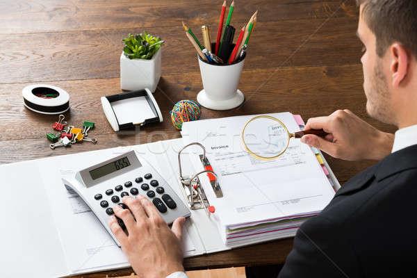 Businessman Inspecting Invoice At Desk Stock photo © AndreyPopov