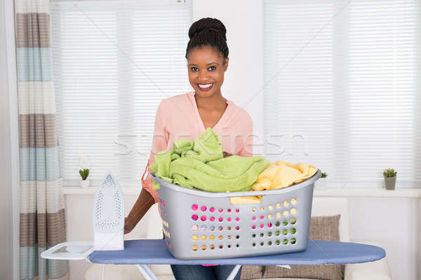 Woman With Iron And Clothes In Basket Stock photo © AndreyPopov