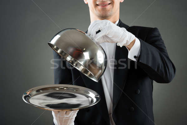 Midsection Of Waiter Holding Cloche Over Empty Tray Stock photo © AndreyPopov