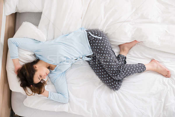 Young Woman Sleeping On Bed Stock photo © AndreyPopov
