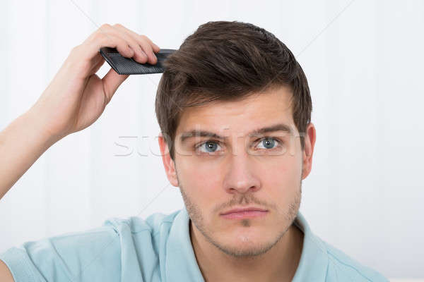 Man Combing His Hair With Comb Stock photo © AndreyPopov