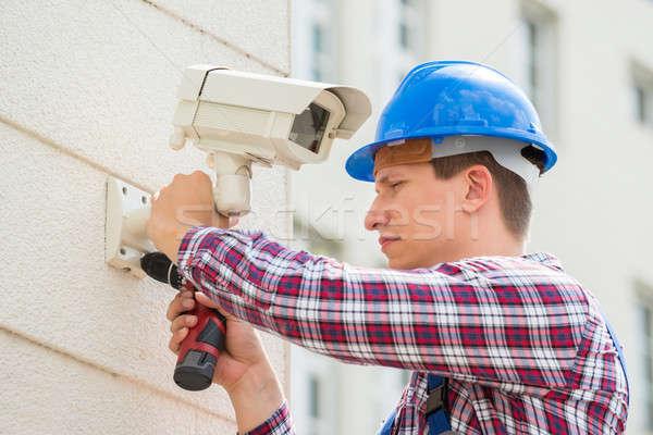 Technikus installál kamera fal fiatal férfi Stock fotó © AndreyPopov