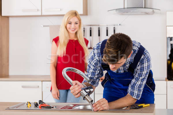 Male Repairman Installing Faucet Of Kitchen Sink Stock photo © AndreyPopov