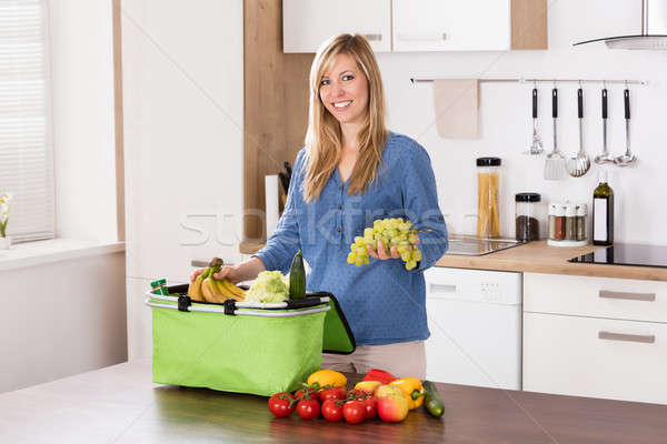 Smiling Woman Removing Grapes From Grocery Bag Stock photo © AndreyPopov