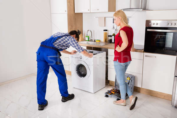 Male Worker Repairing Washer In Kitchen Room Stock photo © AndreyPopov