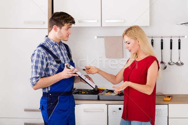 Woman Arguing With Plumber Over Bill In The Kitchen Stock photo © AndreyPopov