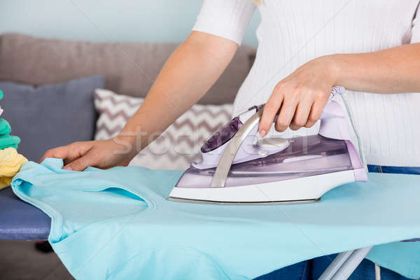Maid Ironing Clothes On Ironing Board Stock photo © AndreyPopov