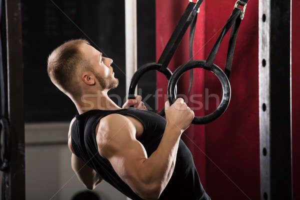 Fitnessz férfi húz felfelé gimnasztikai gyűrűk Stock fotó © AndreyPopov