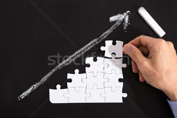 Person Arranging Puzzles On Blackboard Stock photo © AndreyPopov