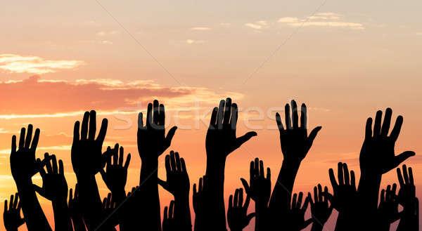 Silhueta as mãos levantadas dramático céu pôr do sol mãos Foto stock © AndreyPopov