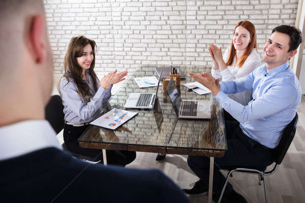 Coworkers Clapping In Meeting Stock photo © AndreyPopov
